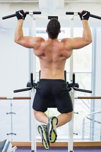 Shirtless bodybuilder doing pull ups